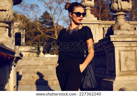 fashion outdoor photo of beautiful young woman with dark hair in elegant clothes and sunglasses posing in sunny autumn park - stock photo