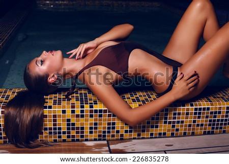 fashion outdoor photo of beautiful young woman with dark hair in elegant swimsuit posing beside a night swimming pool - stock photo