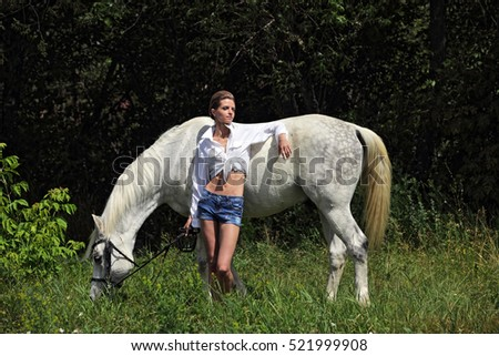 Fashion outdoor photo of beautiful young woman with horse,walking by summer woods