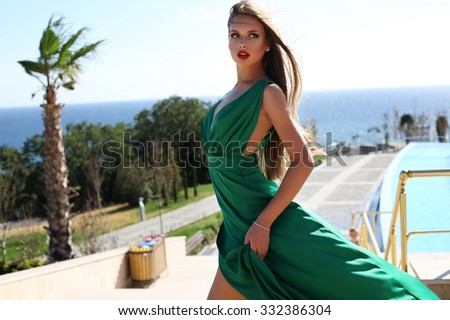 fashion outdoor photo of beautiful young woman with long blond hair in luxurious green silk dress posing beside swimming pool  - stock photo