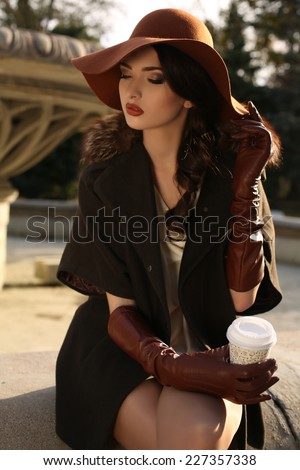 fashion outdoor photo of elegant brunette woman wearing coat with fur,felt hat and leather gloves,holding a paper cup of coffee in hand,sitting beside a fountain in autumn park - stock photo