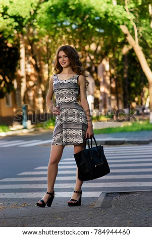 Fashion outdoor photo of gorgeous sensual woman in elegant skirt with handbag at summer street.
