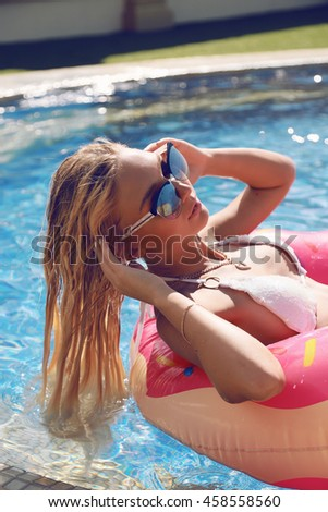 fashion outdoor photo of gorgeous sexy woman with blond hair in elegant bikini relaxing beside swimming pool