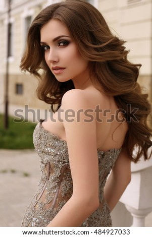 fashion outdoor photo of gorgeous woman with dark curly hair in luxurious sequin dress