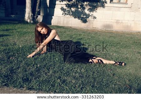 fashion outdoor photo of gorgeous woman with dark hair wears luxurious black dress and accessories,posing beside antic villa,lying on grass