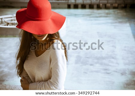 fashion outdoor photo of gorgeous woman with long hair wears luxurious red hat and sitting by the pool. Focus on a hat. Vintage and fashion style. Outdoors shot, horizontal - stock photo