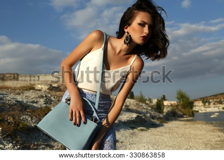 fashion outdoor photo of gorgeous young woman with short dark hair wears elegant dress,posing on summer beach,holding bag in hands  - stock photo