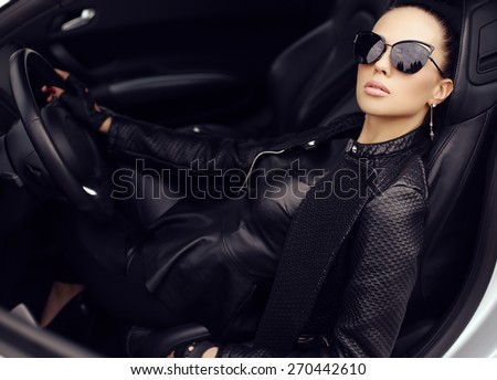 fashion outdoor photo of sexy beautiful woman with dark hair in black leather jacket and sunglasses posing in luxurious auto   - stock photo