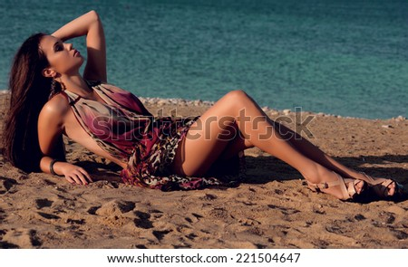 fashion outdoor photo of sexy beautiful woman with dark hair in elegant dress relaxing on summer beach