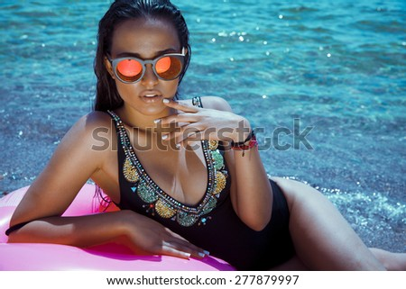 fashion outdoor photo of sexy beautiful woman with long hair in elegant black bikini with accessories relaxing on summer beach. horizontal shot