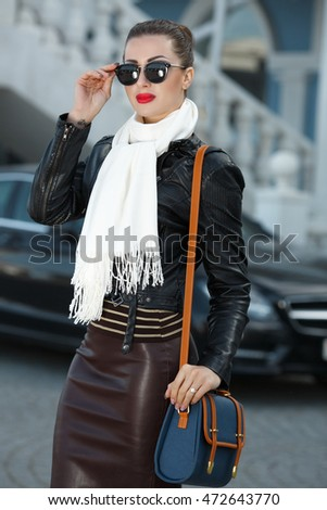 Fashion outdoor photo of sexy brunette woman in autumn leather jacket and bag. Fashionable girl in sunglasses posing at city street.