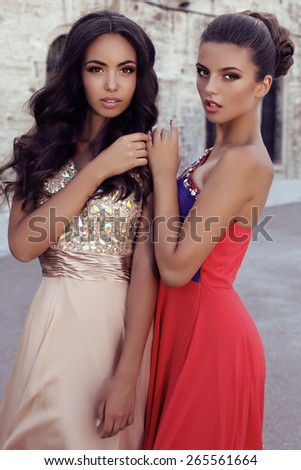 fashion outdoor photo of two beautiful girls with dark hair in luxurious dresses posing beside old castle  - stock photo