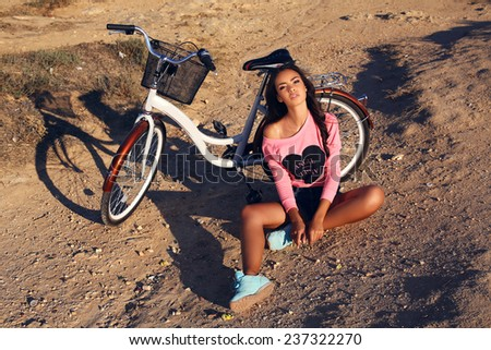 fashion outdoor photo of young beautiful woman with dark hair and tanned skin sitting beside a bicycle on summer beach - stock photo