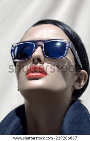 Fashion outdoor portrait of a young beautiful brunette girl in sunglasses with stylish hairstyle.