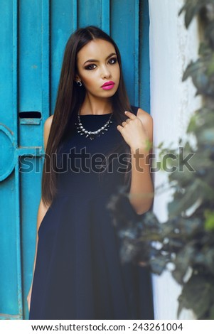 fashion outdoor portrait of beautiful elegant lady with dark long hair and bright evening make up wearing blue dress earrings and necklace, posing on the background of blue door