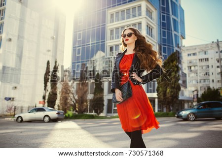 Fashion outdoor portrait of gorgeous long hair woman in elegant red dress and black leather jacket - autumn style. Fashionable hipster girl in trendy clothes posing at city street lifestyle portrait.