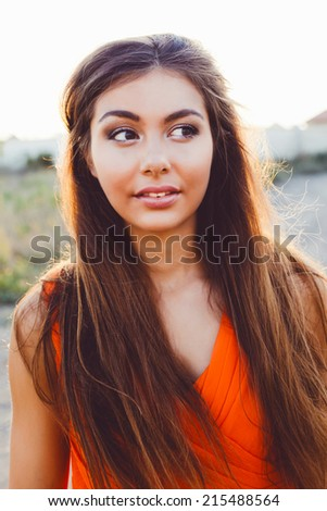 Fashion outdoor portrait of pretty woman wit amazing long straight brunette hairs big brown eyes and full sensual lips posing at countryside on sunset, wearing bright orange dress. - stock photo