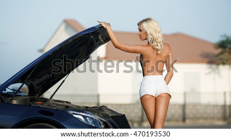 Fashion outdoor portrait of sexy blonde woman in shorts at luxury car