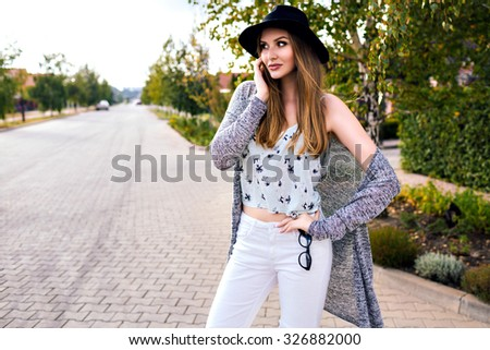 Fashion outdoor portrait of young pretty sensual blonde woman posing at countryside at autumn time, wearing stylish hipster casual ought and hat, soft vintage colors, walking alone. - stock photo