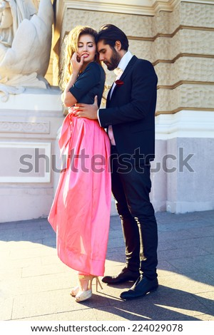 Fashion outdoor portrait of young stylish elegant sexy couple posing at the street. Wearing elegant glamour evening suit and maxi dress, bright sunny colors. First romantic date. - stock photo