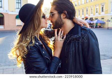 Fashion outdoor sensual romantic portrait of beautiful young couple hugs and kissing on the stereo of european city. Wearing trendy fall black outfits, rock n roll style. Bright evening sunlight. - stock photo