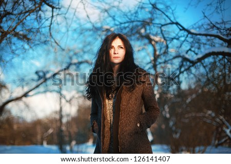 Fashion outdoor spring portrait of pretty girl in garden. Woman posing in winter park.