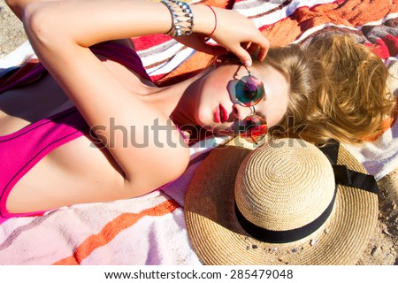 Fashion outdoor travel photo of sexy beautiful woman with blond hair in elegant summer bikini and accessories,summer mirrored sunglasses and travel hat,relaxing on tropical summer beach,summer colors - stock photo