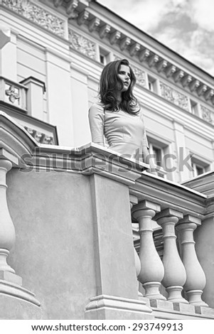 fashion outside shoot of very pretty woman with elegant pink dress and long natural hair posing on balcony of ancient palace,black and white image