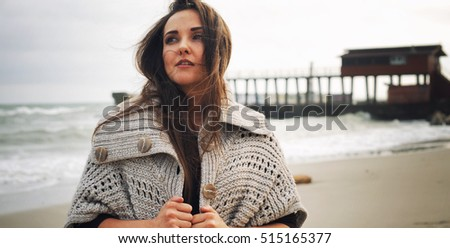 Fashion pensive woman portrait against a pier on a sea beach, knitted coat with big buttons, autumn outdoor fashion