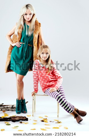 Fashion photo of attractive mother and young daughter. Autumn style.  - stock photo