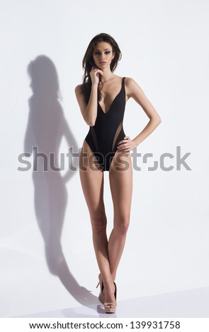 Fashion photo of beautiful and young lady in swimsuits posing in studio - stock photo