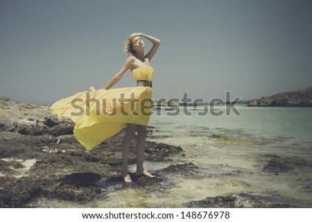 Fashion photo of beautiful lady in yellow dress on the sea