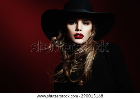 Fashion photo of beautiful model  in elegant hat and sunglasses posing on red background. Beauty closeup portrait. - stock photo