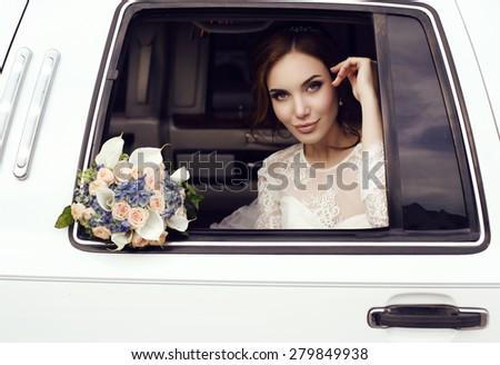 fashion photo of beautiful sensual bride with dark hair in elegant lace wedding dress posing in car - stock photo