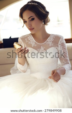 fashion photo of beautiful sensual bride with dark hair in luxurious lace wedding dress posing on yacht - stock photo