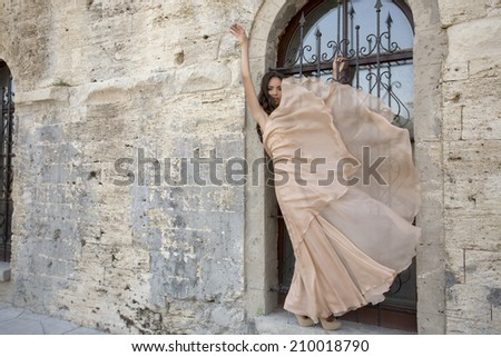fashion photo of beautiful sensual girl with long dark hair in elegant beige dress posing beside an antic wall of castle