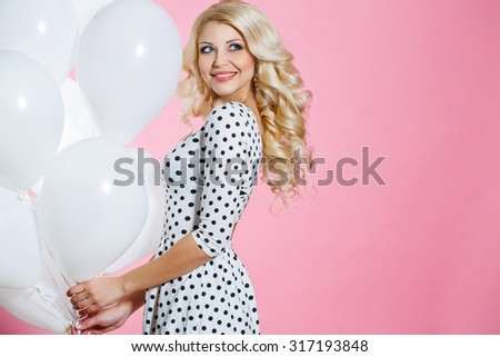 Fashion photo of beautiful woman with balloons. Girl posing. Studio photo. Attractive blonde elegant woman with balloons over pink background. - stock photo