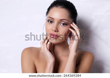 fashion photo of beautiful woman with dark hair with natural makeup and radiance health skin posing in studio - stock photo
