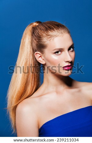 Fashion photo of beautiful woman with ponytail. Beauty woman on blue background - stock photo