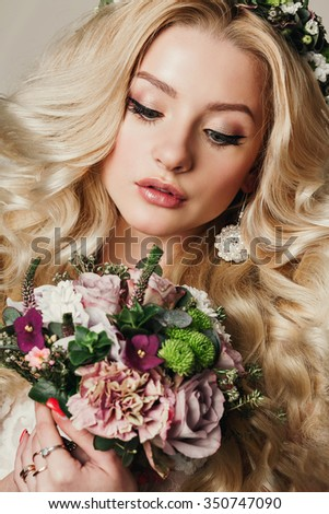 Fashion photo of beautiful young girl with long curly hair. Jewelry. Hairstyle. Vogue. Glamour Makeup. Fashionable blonde posing, looking at camera. Studio shot.bride with bouquet of flowers, wreaths - stock photo