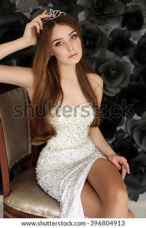 fashion photo of beautiful young woman with dark hair wears elegant dress and precious crown,posing in studio