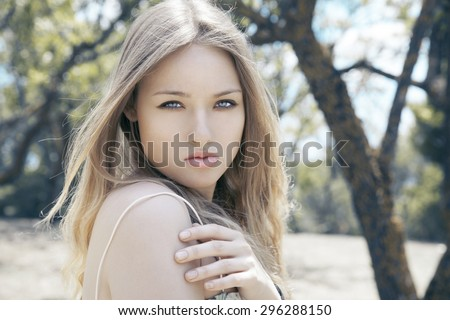 Fashion photo of blonde beauty with natural make up and long hair. Autumn portrait. Horizontal, outdoors shot. - stock photo