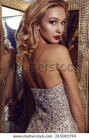 fashion photo of gorgeous woman with blond hair  in elegant dress posing in luxurious interior