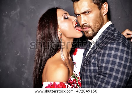 Fashion photo of handsome elegant man in suit with beautiful sexy woman licking man's cheek and posing near gray wall