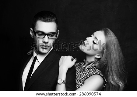 Fashion photo of office romance of sexy young lovers of beautiful blond woman and handsome brunette businessman wearing in format suit,tie,glasses, they are hugging and kissing on Valentine's day - stock photo