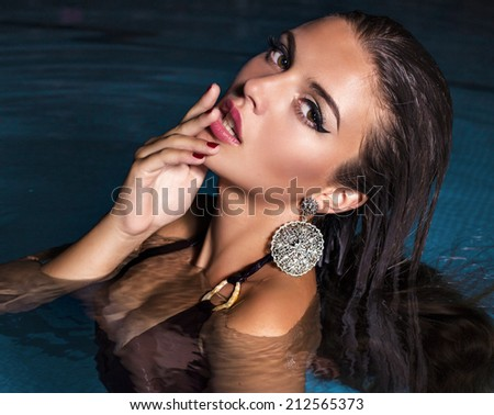 fashion photo of sexy beautiful girl with dark hair in bikini relaxing in swimming pool at night