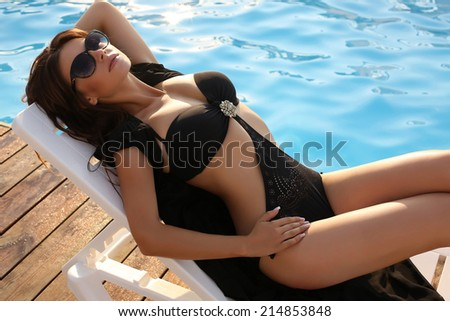 fashion photo of sexy beautiful girl with dark hair in elegant swimsuit relaxing beside a swimming pool - stock photo