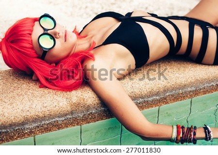 Fashion photo of sexy beautiful girl with red wig hair in black bikini and sunglasses relaxing beside a swimming pool. Outdoors lifestyle portrait - stock photo