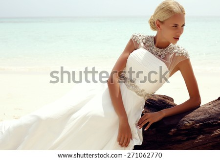 fashion photo of sexy beautiful woman with blond hair in elegant wedding dress posing on tropical beach in Thailand   - stock photo