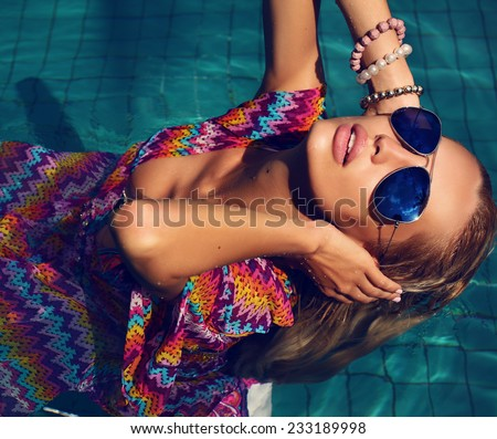 fashion photo of sexy beautiful woman with blond wet hair in aviator sunglasses posing in swimming pool - stock photo